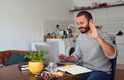Buy stock photo Shot of a young man making a video call on a laptop at home