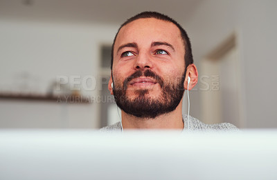 Buy stock photo Shot of a young man wearing earphones while using a laptop at home