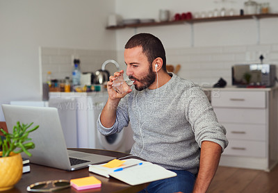 Buy stock photo Shot of a young man drinking water while working on a laptop at home