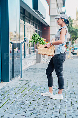 Buy stock photo Portrait of a young woman delivering a crate full of groceries