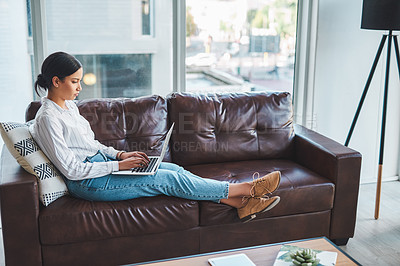 Buy stock photo Shot of a young woman using a laptop on the sofa while working from home