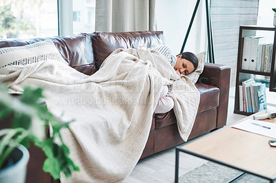 Buy stock photo Shot of a young woman feeling sick on the sofa at home