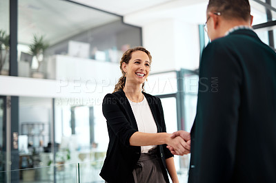 Buy stock photo Shot of a businesswoman and businessman shaking hands in a modern office
