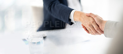 Buy stock photo Shot of two businesswomen shaking hands in a modern office