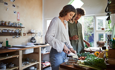 Buy stock photo Cropped shot of a young couple cooking together in the kitchen at home