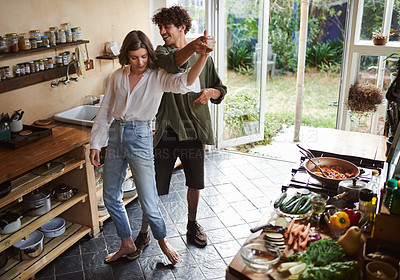 Buy stock photo Shot of a young couple dancing while cooking together at home