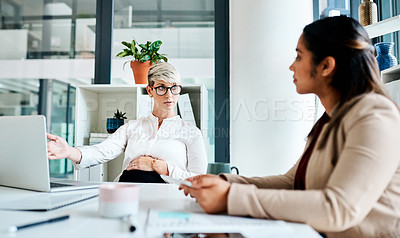 Buy stock photo Shot of a pregnant businesswoman having a discussion with her colleague in an office