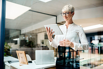 Buy stock photo Shot of a pregnant businesswoman using a digital tablet in an office