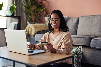 Buy stock photo Shot of a young woman using a laptop and credit card in the living room at home