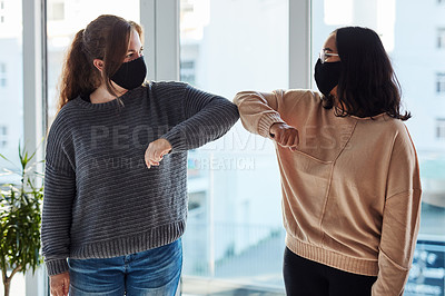 Buy stock photo Shot of two young women bumping elbows in a modern office