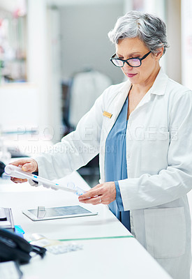 Buy stock photo Shot of a mature pharmacist filling a prescription of capsules in a chemist
