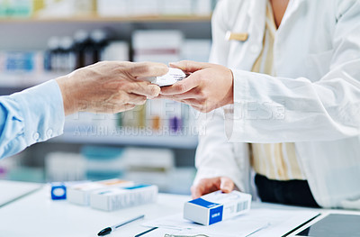 Buy stock photo Shot of a pharmacist handing a customer a box of medication in a chemist