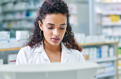 Buy stock photo Shot of a young woman using a computer while working in a pharmacy