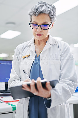 Buy stock photo Shot of a mature woman filling out paperwork while working in a pharmacy