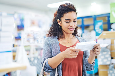 Buy stock photo Shot of a young woman reading the label on a box of medicine in a pharmacy
