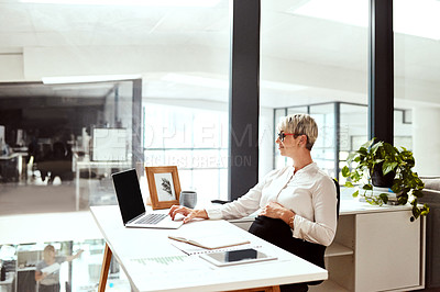 Buy stock photo Shot of a pregnant businesswoman working on a laptop in an office