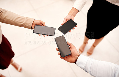 Buy stock photo Closeup shot of a group of unrecognisable businesspeople holding cellphones