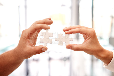 Buy stock photo Closeup shot of two unrecognisable businesspeople holding puzzle pieces together