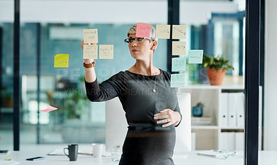 Buy stock photo Shot of a pregnant businesswoman brainstorming with notes on a glass wall in an office