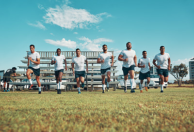 Buy stock photo Rearview shot of a group of young rugby players running on a field