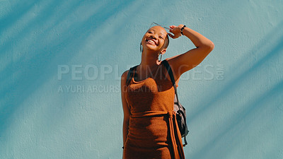 Buy stock photo Shot of an attractive young woman posing against a blue wall outdoors