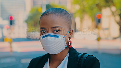 Buy stock photo Shot of a young businesswoman wearing a mask against an urban background