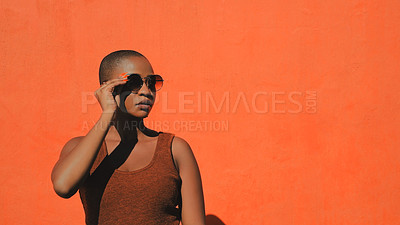 Buy stock photo Shot of an attractive young woman posing against an orange wall outdoors