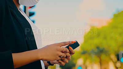 Buy stock photo Cropped shot of a businesswoman wearing a mask and using a smartphone against an urban background