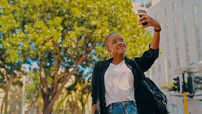 Buy stock photo Shot of a young businesswoman taking selfies against an urban background