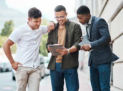 Buy stock photo Shot of a group young businessmen using a digital tablet together against an urban background
