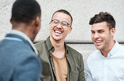 Buy stock photo Shot of three young businessmen having a discussion against an urban background
