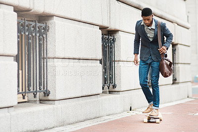 Buy stock photo Shot of a young businessman riding a skateboard through the city