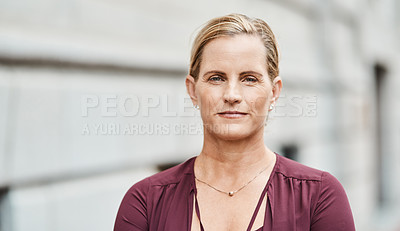 Buy stock photo Portrait of a mature businesswoman standing against an urban background