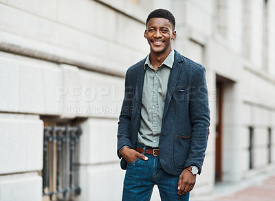 Buy stock photo Portrait of a confident young businessman standing against an urban background