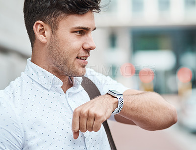 Buy stock photo Shot of a young businessman using a smartwatch against an urban background