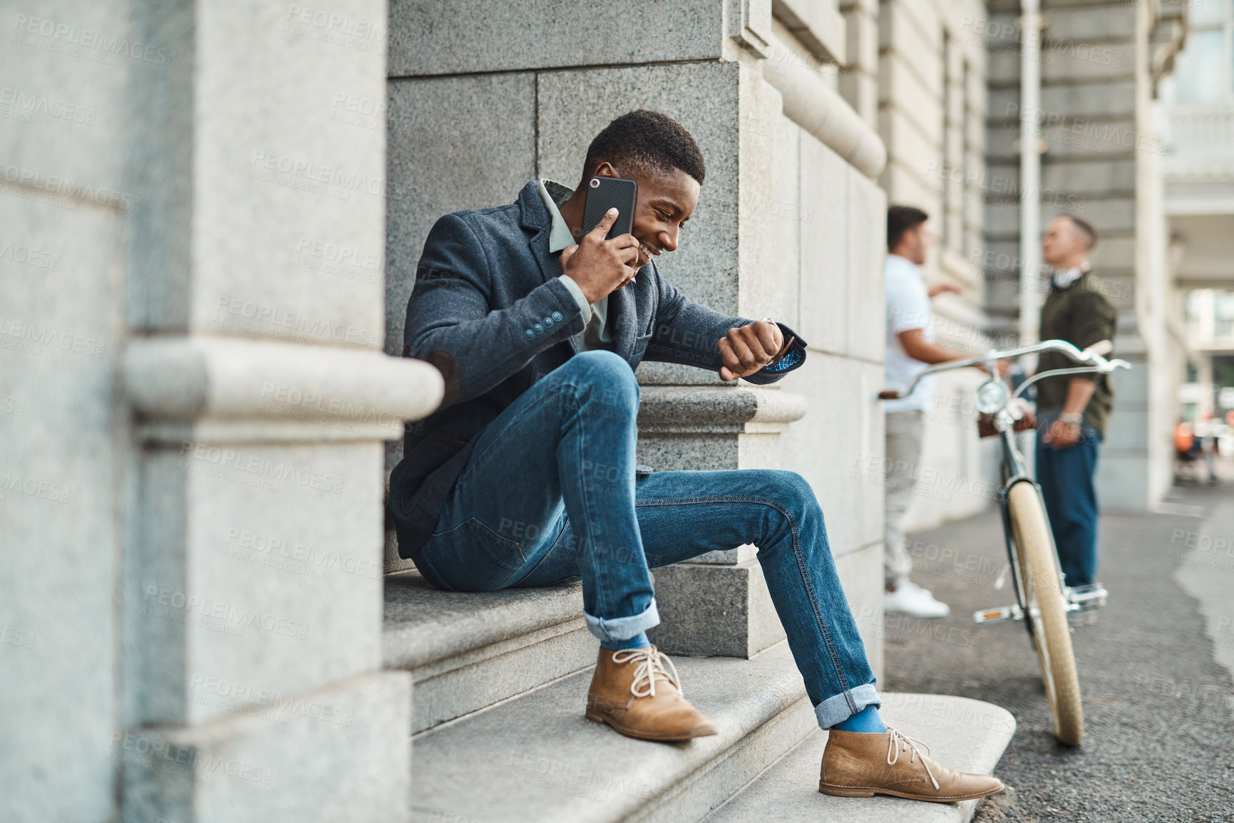 Buy stock photo Shot of a young businessman using a smartphone and checking the time against an urban background