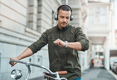 Buy stock photo Shot of a young businessman looking at his watch while riding a bicycle in the city