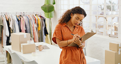 Buy stock photo Shot of a young woman making notes on clipboard in a design studio
