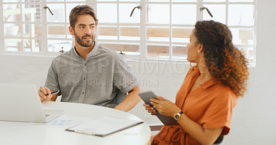 Buy stock photo Shot of a young businessman and businesswoman using wireless technology during a meeting in a modern office