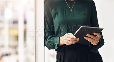 Buy stock photo Cropped portrait of an unrecognizable young businesswoman using her tablet while standing in the office