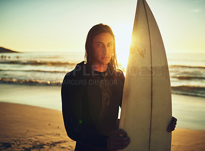 Buy stock photo Portrait of a young man standing with a surfboard at the beach
