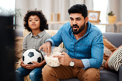Buy stock photo Cropped shot of an adorable little boy watching a football game with his father on tv at home