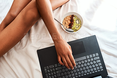 Buy stock photo Cropped shot of an unrecognizable woman sitting on her bed with her laptop and a bowl of oats