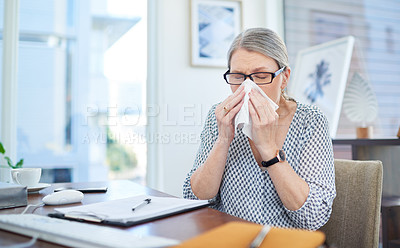 Buy stock photo Shot of a mature businesswoman blowing her nose in an office