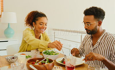 Buy stock photo Shot of a young man and woman having lunch together at home