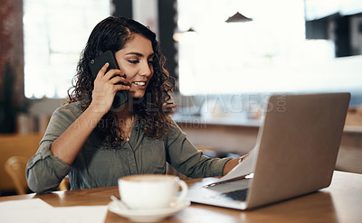 Buy stock photo Shot of a young woman using a laptop and smartphone while working in a cafe