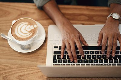 Buy stock photo High angle shot of an unrecognisable woman using a laptop and having coffee in a cafe