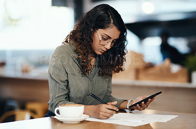 Buy stock photo Shot of a young woman using a smartphone and going over paperwork in a cafe