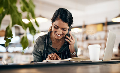 Buy stock photo Shot of a young woman using a smartphone while working in a cafe