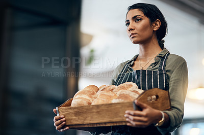 Buy stock photo Shot of a young woman holding a selection of freshly baked breads in her bakery